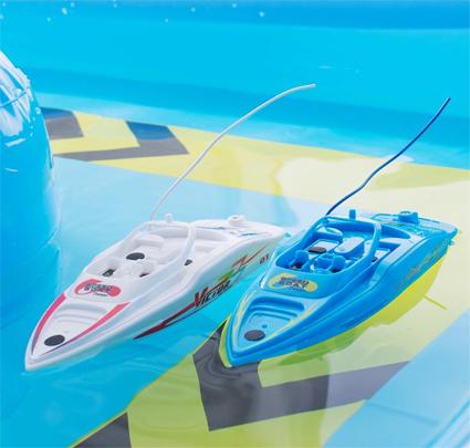 To fjernstyrte racingbåter med basseng.
