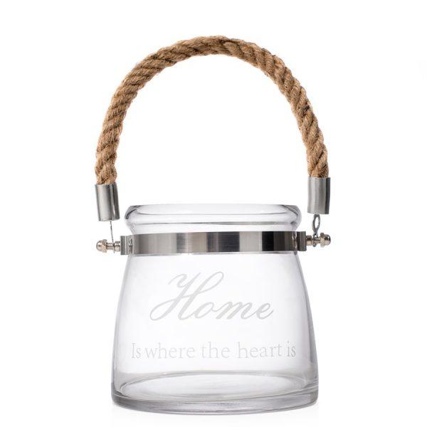 """Glasslykt Glasslykten har flettet håndtak og skriften """"Home is where the heart is""""."""