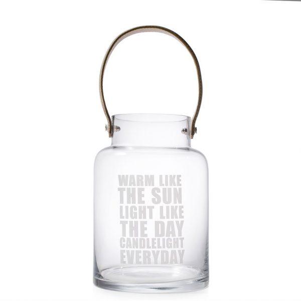 """Glasslykt Denne glasslykten har lys skinnreim og skriften """"warm like the sun, light like the day, candlelight everyday""""."""